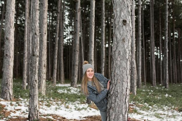 Mujer de tiro medio posando con árbol