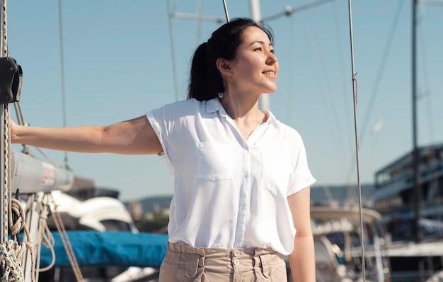 Mujer de tiro medio posando en el puerto