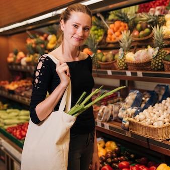 Mujer de tiro medio posando en una tienda de comestibles