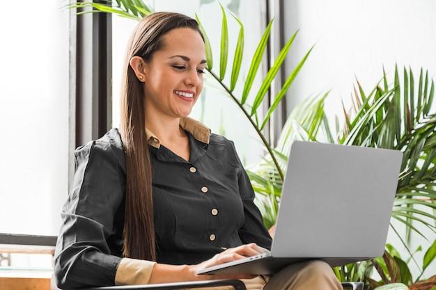 Mujer de tiro medio que comprueba estadísticas en la computadora portátil
