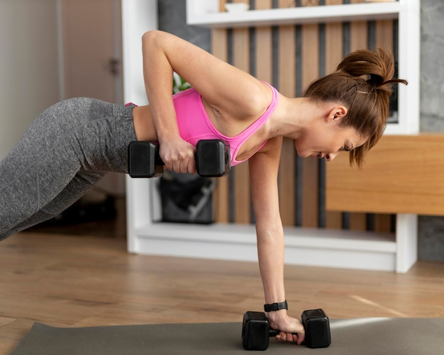 Mujer de tiro medio que trabaja con pesas