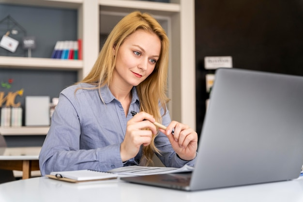 Mujer de tiro medio que trabaja con el portátil