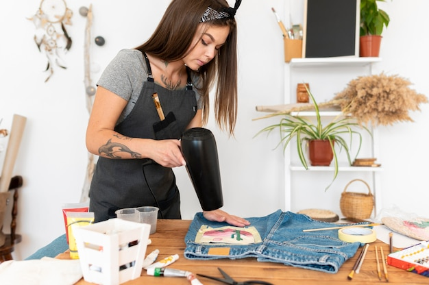 Mujer de tiro medio secar los pantalones