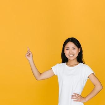 Mujer de tiro medio sonriente apuntando hacia arriba