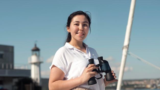 Mujer de tiro medio sosteniendo binoculares