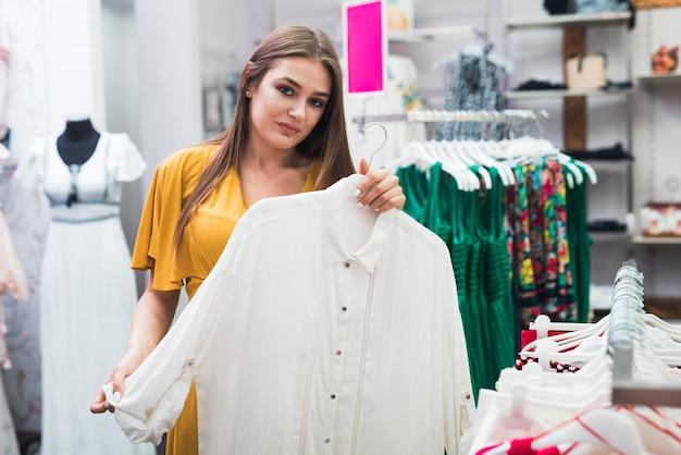 Mujer de tiro medio sosteniendo una camisa blanca.