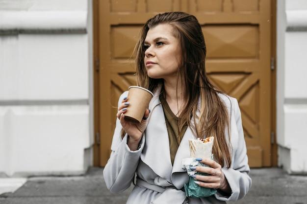 Mujer de tiro medio sosteniendo kebab