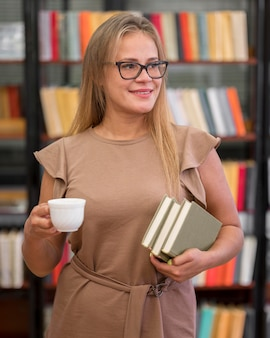 Mujer de tiro medio sosteniendo libros