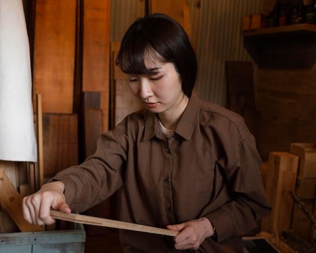 Mujer de tiro medio sosteniendo un pedazo de madera
