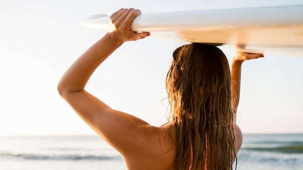 Mujer de tiro medio sosteniendo la tabla de surf