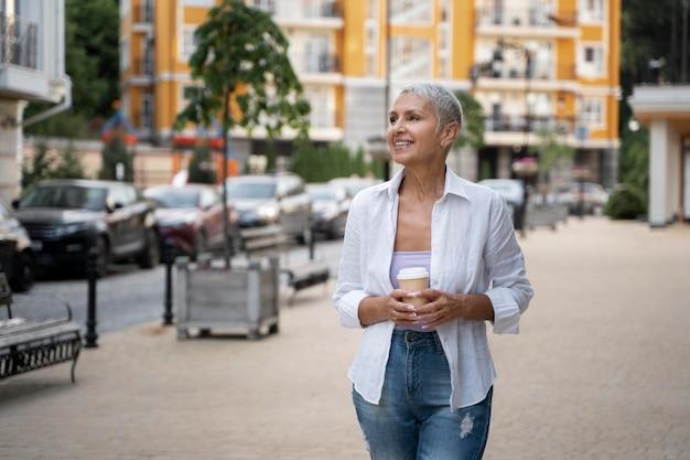 Mujer de tiro medio sosteniendo la taza de café