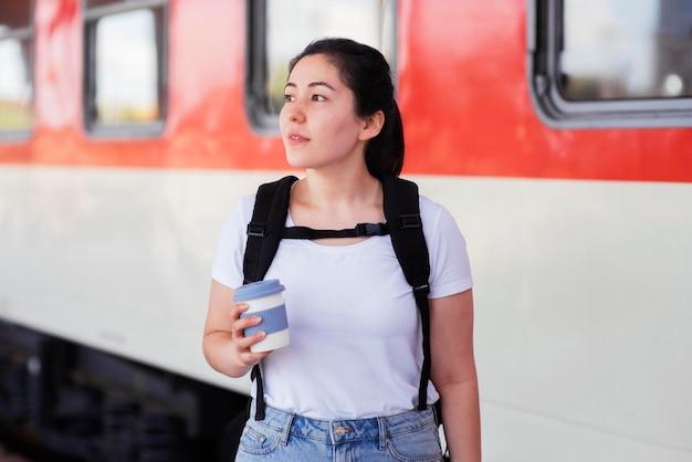 Mujer de tiro medio con taza en la estación de tren