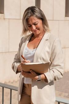 Mujer de tiro medio tomando notas