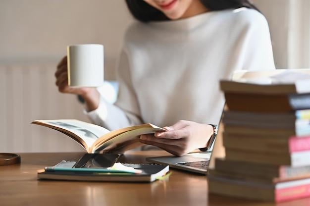 Mujer de tiro recortada con taza de café mientras lee el libro.