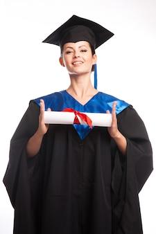 Una mujer con un título en la mano mientras mira a la cámara.