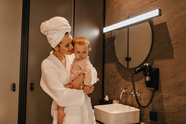 Mujer con toalla blanca en la cabeza y bata de baño está sonriendo y posando con el bebé en el baño.