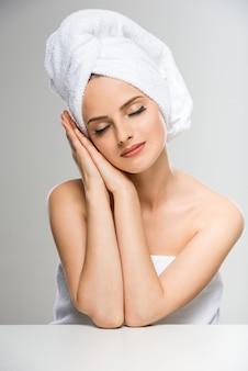 Mujer con una toalla en la cabeza, cerrando los ojos.