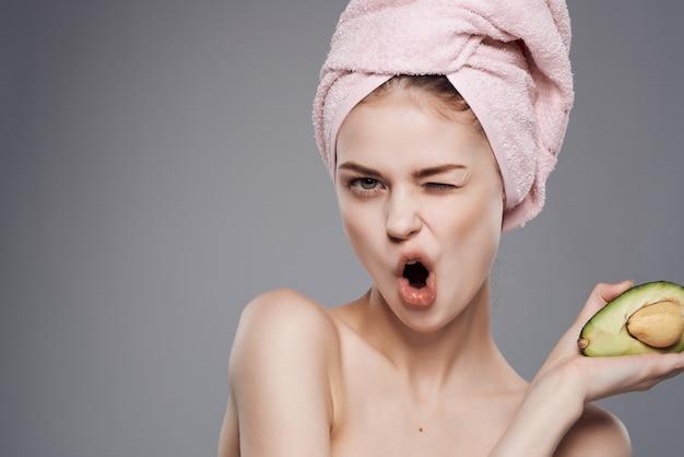 Mujer con toalla en la cabeza, hombros desnudos, fruta de aguacate, vitaminas, salud