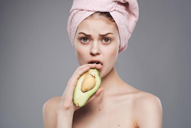 Mujer con una toalla en la cabeza, piel limpia, vitaminas, fondo aislado
