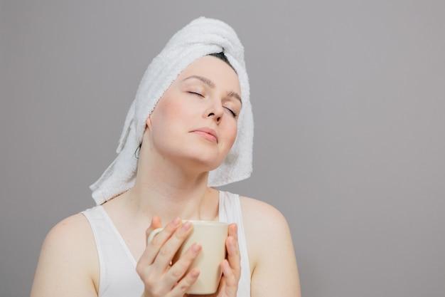Mujer con una toalla sobre su cabeza y una taza