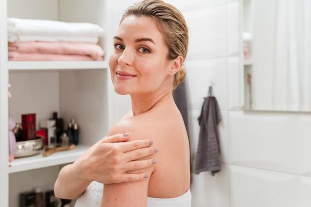 Mujer en toalla sosteniendo su brazo