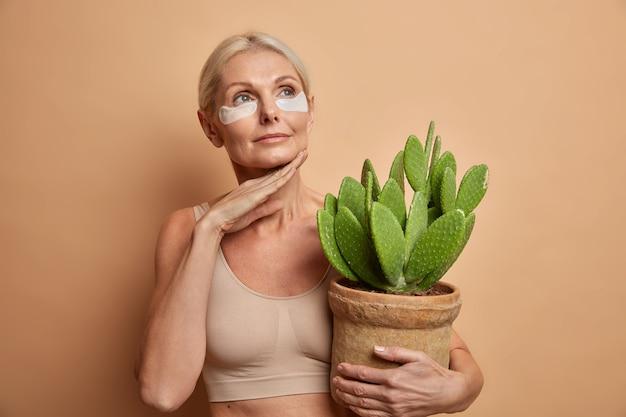 Mujer toca la línea de la mandíbula aplica suavemente parches de colágeno debajo de los ojos sostiene cactus en macetas viste top aislado en marrón