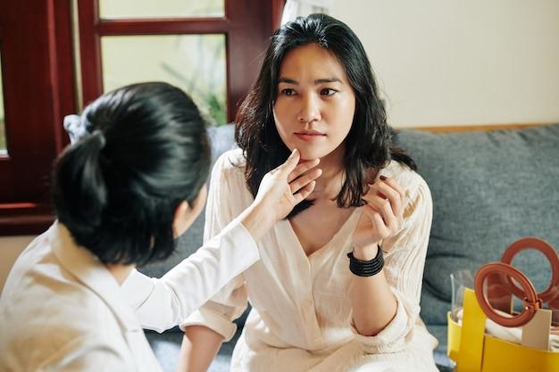 Mujer tocando la barbilla de su amiga