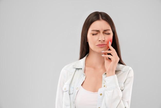 Mujer tocando la boca por dolor de muelas