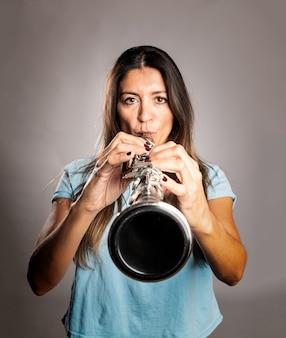 Mujer tocando un clarinete en gris