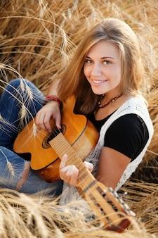 Mujer tocando la guitarra en un campo de trigo