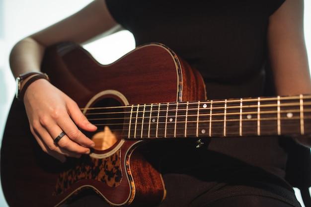 Mujer tocando una guitarra en la escuela de música