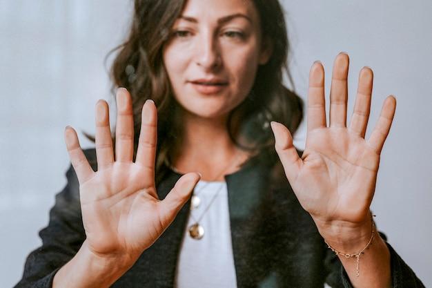 Mujer tocando una pantalla con la palma de su mano