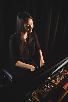 Mujer tocando el piano en el estudio de música
