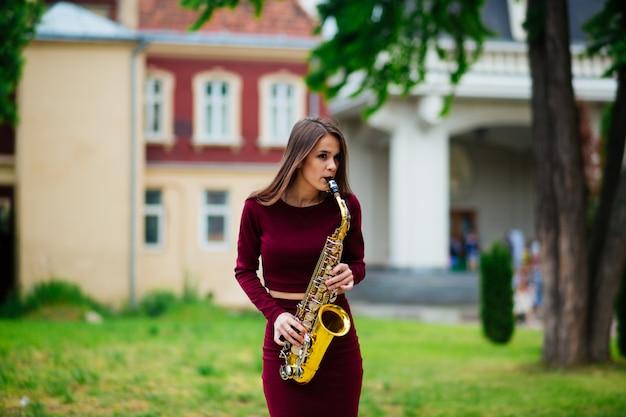 Mujer tocando el saxofón en las calles de la ciudad.