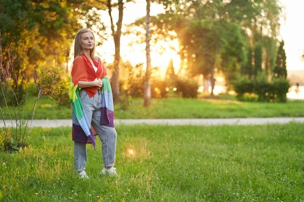 Mujer tolerante sosteniendo la bandera lgbt sobre los hombros