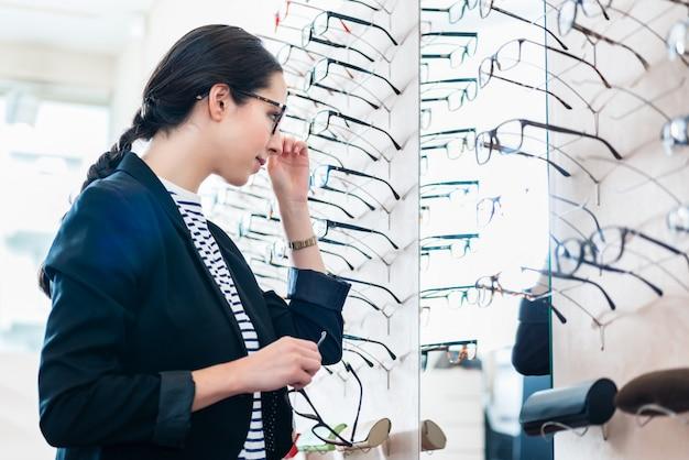 Mujer, toma, anteojos, de, estante, en, óptica, tienda