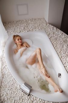 La mujer toma el baño con espuma por la mañana. jacuzzi