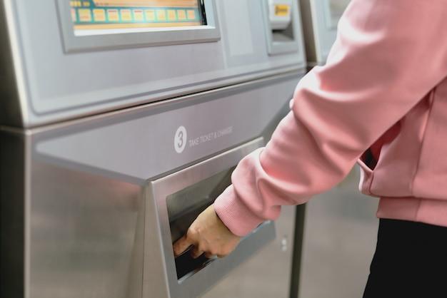 La mujer toma un boleto de tren después de comprar desde la máquina de boletos de metro.