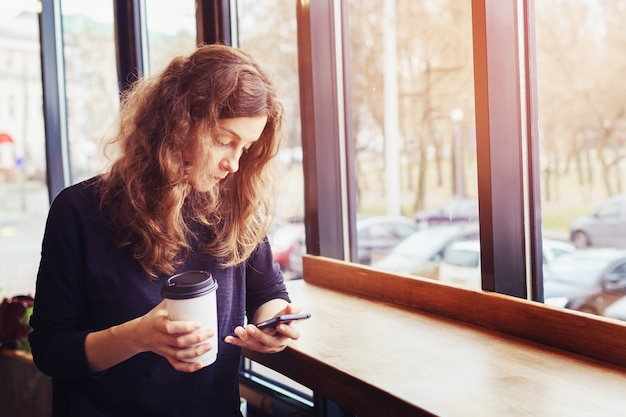 Una mujer toma café en una cafetería y usa el teléfono.