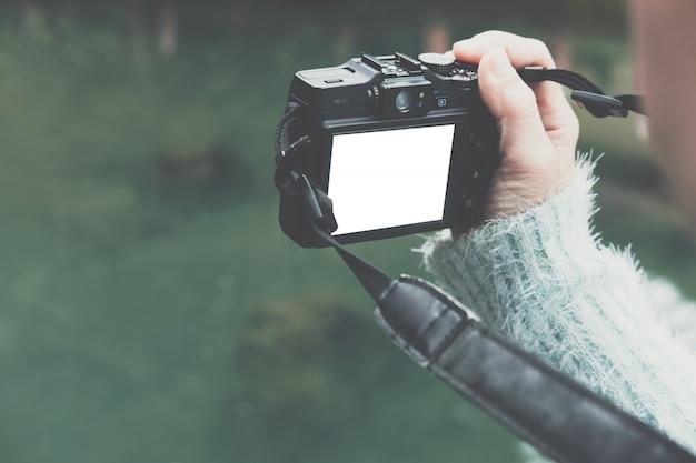 La mujer toma la foto del estanque tranquilo verde en el parque.