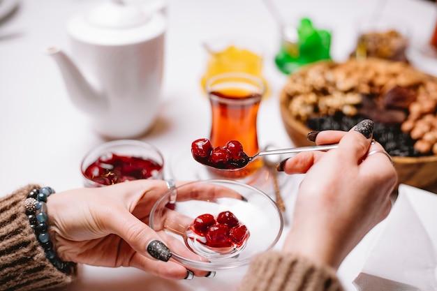 Mujer toma té de mermelada de cerezas en vista lateral armudy