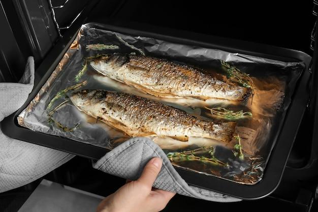 Mujer tomando la bandeja para hornear con pescado fuera del horno
