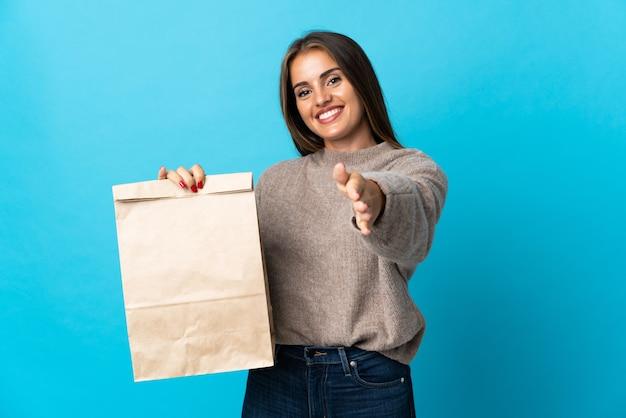 Mujer tomando una bolsa de comida para llevar aislado sobre fondo azul un apretón de manos para cerrar un buen trato