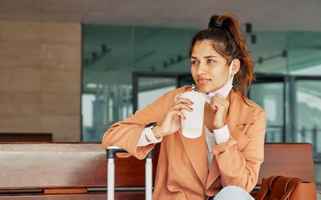 Mujer tomando café en el aeropuerto durante la pandemia