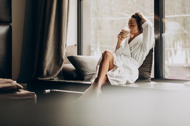 Mujer tomando café en bata de baño junto a la ventana en casa