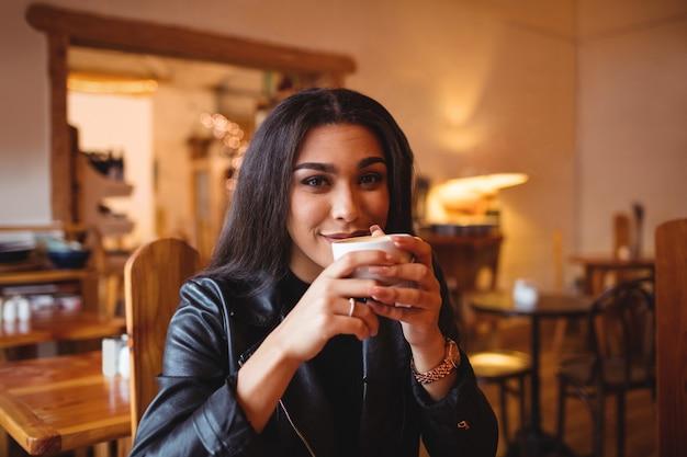 Mujer tomando café en la cafetería.