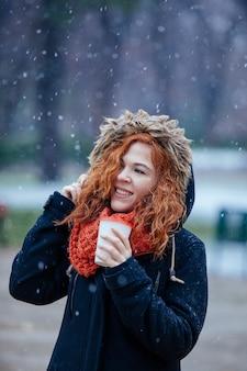 Mujer tomando café en un día nevado de invierno