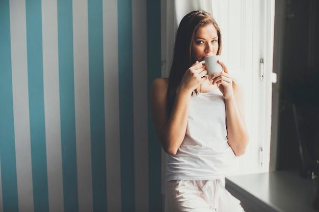 Mujer tomando café junto a la ventana durante el día
