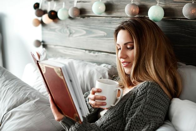 Mujer tomando café y leyendo un libro en la cama
