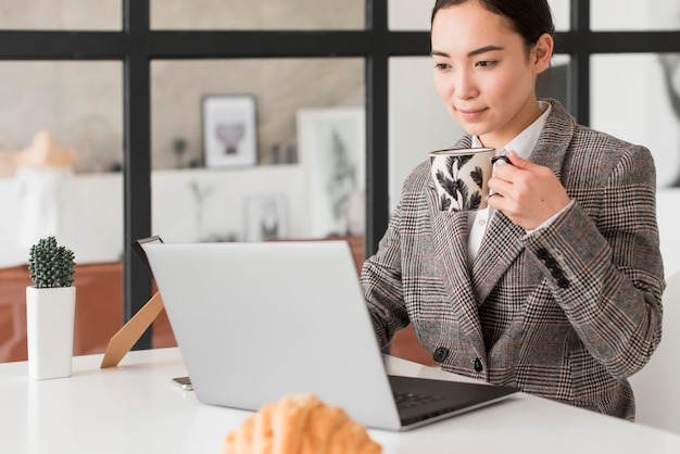 Mujer tomando café mientras trabaja
